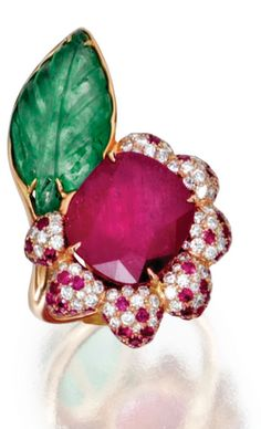 18 KARAT PINK GOLD, RUBY, EMERALD AND DIAMOND FLOWER RING Set in the center with a cushion-shaped ruby weighing approximately 11.00 carats, the petals pavé-set with small round diamonds weighing approximately .45 carat and small round rubies, accented by a carved emerald leaf weighing approximately 4.25 carats, size 6.