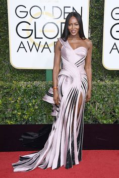 Naomi Campbell was gorgeous in a gown from the Atelier Versace Fall 2016 runway at the 2017 #GoldenGlobes ceremony. She wore a pearl pink gown with asymmetrical neckline, ribbon-like construction, and exaggerated hip detail, adorned with black Swarovski crystals.