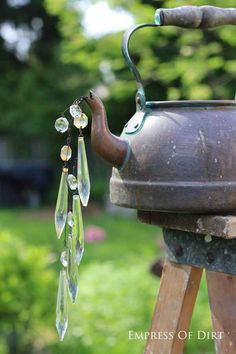 Try using my silver teapots Gallery of watering can garden art ideas - old kettles can be used as well