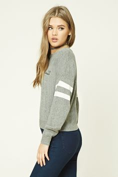 """A heathered knit sweater featuring a """"Not Interested"""" embroidered chest graphic, a crew neckline, dropped long sleeves with varsity stripes, and a ribbed trim."""