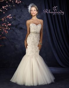 Rhapsody  Style #R7300  Stunning sheath with trumpeting skirt of netting over layers of glitter net, organza and rich duchess satin. The bodice is of silver sequins on embroidered floral appliqués on net over glitter netting. There is a pretty sweetheart neckline and a rhinestone and beaded appliqué belt as well as a chapel train.