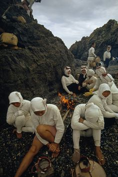 Ama divers warm themselves beside an early morning fire, Japan. Photo: Luis Marden. °