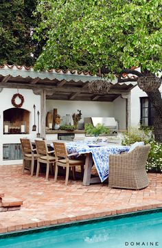 Backyard dining area with blue and white tablecloth, brick pavers, and outdoor kitchen.
