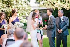 Confederate Home wedding. Bride takes time to smell the roses that the mothers gave them during garden wedding ceremony. © Carolina Photosmith