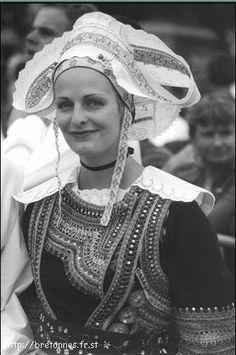 Costume de St Evarzec constitué d'un gilet à manches longues, d'un corselet, d'une jupe en drap de laine noir ornés de broderies aux fils de couleurs vives et de galons métalliques, et d'un tablier en soierie. Le tablier était agrémenté d'une cocarde portée lors du mariage de la jeune fille. Le haut du costume est surmonté d'une collerette, caractéristique du pays Aven, en coton blanc finement plissé.La jupe est portée sur un ou plusieurs jupons de couleurs vives dépassant légèrement de la…