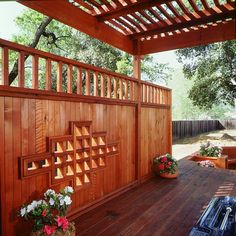 The stunning cutout detailing of this redwood fence complements the shade structure above it.  from California Redwood Association