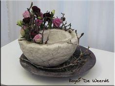 2 piepschuim halve bollen asymmetrisch in elkaar geplaatst en bekleed met klei. Magnoliatakjes in de klei gestoken met kleurige bloemen.