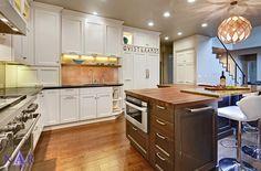 Nar Fine Carpentry, Inc. Sacramento El Dorado Hills. Classic white kitchen. Glass panel backsplash in copper hue compliments the cabinet hardware and sculptural pendant.