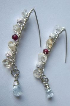 A brand new style of multiple gemstones woven onto a silver hoop.  The gemstones are citrine, garnet, silver balls, and aquamarine.