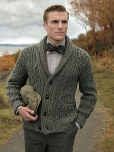 Tap into refined, elegant style with an army green knit cardigan and dark grey wool trousers.  Shop this look for $123:  http://lookastic.com/men/looks/cardigan-long-sleeve-shirt-bow-tie-dress-pants-flat-cap/7442  — Olive Knit Cardigan  — Grey Long Sleeve Shirt  — Brown Plaid Bow-tie  — Charcoal Wool Dress Pants  — Tan Plaid Flat Cap