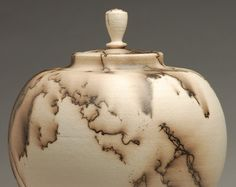 This piece is hand made and horse hair fired by the artist which ensures a truly one of a kind urn. The horse hair firing process requires removing the piece from the kiln at approximately 1200 degrees Fahrenheit, and rapidly placing horse hair on it before it cools. The horse hair burns on the pot leaving a dramatic carbon mark behind. This piece has multiple coats of terra sigillata giving it a soft, luminous sheen. This piece can be used for home decoration or as a funerary urn.  Each…