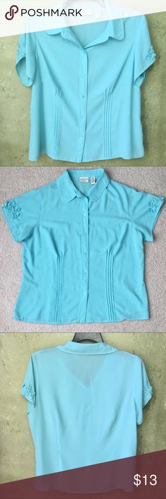 Covington Woman's Blouse Covington Woman's Blouse in a beautiful light blue color in size 16W. Top has a collar v-neck and button downs the front. Has a pretty design on the sleeves and front. Used but good condition. Covington Tops