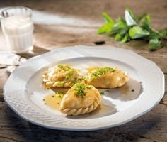 """If made in Carinthia these ravioli-like dumplings are called """"Kärntner Kasnudeln"""" whereas the Tyroleans call them """"Schlutzkrapfen"""". They are either filled with a potato-curd-mixture or with spinach and served with melted butter on top."""
