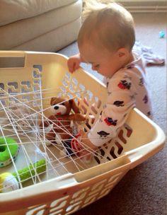 Een spinnenweb maken met touw en was mand. de baby's mogen dan de voorwerpen uit de web proberen eruit te halen.