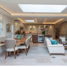 Open-plan kitchen with island unit, wooden dining table and neutral upholstered chairs