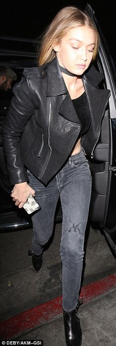 Rocker look: The model wore a leather motorcycle jacket and flashed her toned abs in a tin...