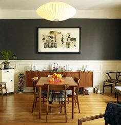 Cool dining room - love the dark grey wall above white wood.