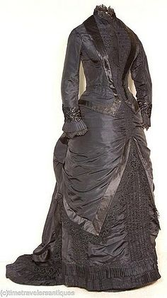 """Front View 1880's original mourning gown. Gown images courtesy of time-travelers antiques on ebay.  """"A most becoming original circa 1880 lady's black silk taffeta 2 piece bustled and trained mourning dress that is a very good example of a woman not sacrificing style at the time of mourning. Lined and stayed, with a ruched bodice and underskirt, trimmed in black silk satin and bobbin and Cluny lace, and with pleated cuffs and hem. Passementerie button accents to the tail, and a graceful…"""