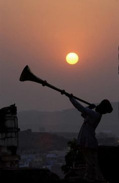 A traditonal Rajasthani musician performs at sunset as he stands on the walls of Mehrangah Fort, India