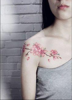 269c827f5 tatuaje hombro, mujer flaca con blusa gris, tatuaje de flor de cerezo en  hombro y clavícula, color rosa