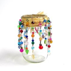 This bohemian style luminary is a mason jar embellished with strands of multicolor glass beads and ribbons. Its the ultimate hippie candle holder! This pint Mason jar has been strung with over 75 multicolor glass beads, all hand wired in a variety of metal finishes into varying lengths of dangles, which have been suspended from raffia wrapped securely around the mouth of the jar. Accented with a pouf of multicolored silk ribbons and a gold dragonfly charm. The outside top edge of the mouth…