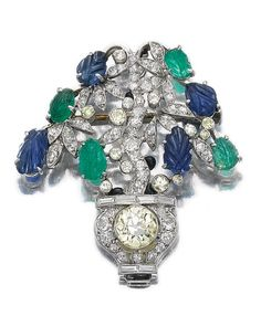 GEM SET, ENAMEL AND DIAMOND BROOCH/PENDANT, CIRCA 1930. Of giardinetto design, set with carved emeralds and sapphires, circular- and single-cut diamonds of yellow and near colourless tint, accented with black enamel, hinged pendent bail.