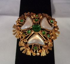 Florenza Vintage Goldtone Brooch with Green & Amber Rhinestones plus Mother of Pearl. You can see the photos in our Vtg Jewelry Store   www.CCCsVintageJewelry.com. Have a great vintage day! Best, Coco