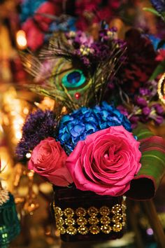 Floral accents and peacock feather decor on a Princess Jasmine inspired table