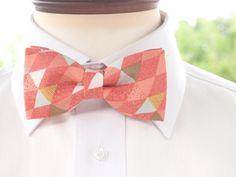お立ち寄りくださりありがとうございます。 蝶ネクタイ専門店の《TATAN》です。今回ご紹介するのは 紅葉のような橙赤色に三角がたくさん描かれた蝶ネクタイです。 三角は暗めの水色や黄色、白、黒などさまざまな色で描かれていて 橙赤色の生地に上手くマッチしています。 まるで秋の紅葉のように見えませんか? シックで上品なデザインはこれからの秋冬にとっても似合いますよ♪男性でも女性でも着用していただけるデザインで、普段使いも可能です。<素材>綿 100%裏地に接着芯を使用しているため、型が崩れにくくなっております。<サイズ> 本体→約10.5cm×5.5cm クリップ→約46mm×7mm<付属品について> 蝶ネクタイ本体の他にクリップを1つお付けしております。 ベルトが必要な方は別途ご購入ください。 こちらより購入が可能です→http://www.snd-tatan.com/items/1842249