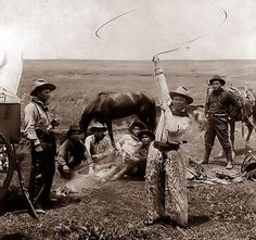 This photograph was taken in 1905. It shows a cowboy in camp, entertaining his friends with rope tricks. The picture was taken some where in Oklahoma.