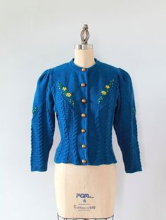 Authentic Austrian 1940s era cardigan sweater in a bright blue wool. Interesting variations in the knit. Form-flattering shape with puffed