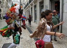 A reveler from the Portuguese village of Aveiro playfully chases a tourist during the Iberian Mask parade in Lisbon May 12, 2012. Traditional masks from northern Portugal and Spain were presented during the parade.