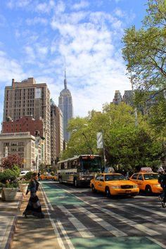 Showing Madison Square Park, near the Flat Iron Bldg traffic criss/cross. New York, New York.