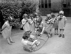 Nursery school children in London wearing their gas masks; WWII