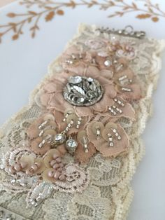 Dusty Blush Vintage Lace Bridal Cuff This beautiful cuff is made with hand dyed lace and embellished with vintage rhinestones, crystals, seed beads and sequins. Textile Jewelry, Fabric Jewelry, Cuff Jewelry, Fabric Bracelets, Lace Bracelet, Bridal Cuff, Bridal Lace, Fabric Beads, Fabric Ribbon