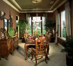 Intimate formal dining room with plenty of design detail including ornate dining table that seats six people, wood buffet to the side, drapes and tray ceiling.