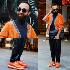 Shop this look on Lookastic:  http://lookastic.com/men/looks/zip-pouch-and-sweatpants-and-turtleneck-and-sunglasses-and-cardigan-and-derby-shoes/4150  — Black Leather Zip Pouch  — Black Leather Sweatpants  — Black Turtleneck  — Black Sunglasses  — Orange Cardigan  — Orange Leather Derby Shoes