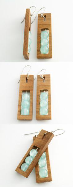 Ręcznie wykonane kolczyki z drewna wiśniowego. W środku zostały zamontowane błękitne koraliki z jadeitu na srebrnym sztyfcie. Bigle zostały wykonane ze stali antyalergicznej. Długość kolczyka – 5cm Szerokość kolczyka – 1,5cm