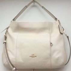 "NWT 🔶 COACH Pebble Leather EW Isabelle ""Chalk"" color Pebble leather. Gold tone hardware. Exterior front hidden zipper pocket.      * Inside zip and two multifunction pockets     * Zip-top closure. Fabric lining     * Handle / Shoulder strap with 11 3/4 drop     * Longer strap with 22 drop for shoulder or crossbody wear.                                      Measures approximately 13"" (L) x 13"" (H) x 3"" (W) Coach Bags Shoulder Bags"