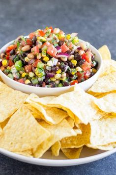Bowl of Cowboy Caviar served with crispy tortilla chips. The Cowboy Caviar is pictured in a white bowl. There is a dark blue background.