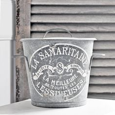 A vintage French zinc wash bucket with its original label and lid