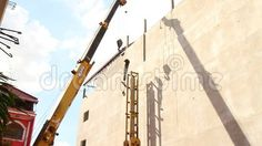 Wide shot of a construction crane lifting a 2nd worker onto the top pf a pile driver frame in Southeast Asia.