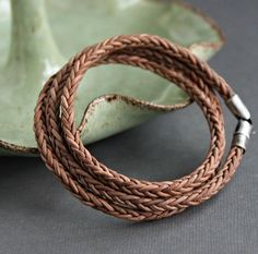 Soft, naturally dyed* light brown leather cord is uniquely square braided and wraps around three times for this handsome mens bracelet. Its secured with solid, sterling silver end caps with a swivel clasp for an easier connection. Silver has been oxidized and sanded for a rustic look.  See this bracelet in dark brown as shown in last photo here https://www.etsy.com/listing/294706439/mens-wrap-bracelet-brown-leather-braid?  Leather braid is 4 mm thick  For the best fit sizes are based on…