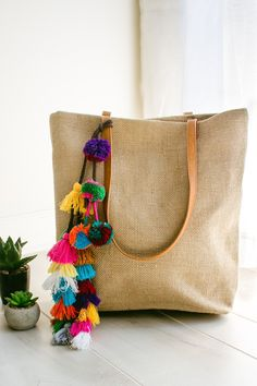 Your go-to summer tote has arrived. A perfectly neutral tan, this darling tote has tassel & pom pom details, long straps for easy carrying, three inner pockets, and a magnetic top closure. Fully lined