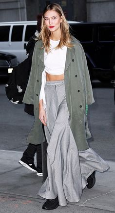 Karlie Kloss wears a crop top, trench coat, wide-leg trousers, and Yeezy Boost sneakers in black