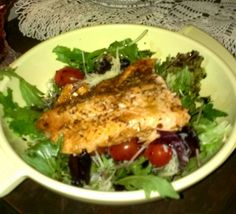 Steelhead trout filet atop leafy greans infused with balsamic vinagrette.