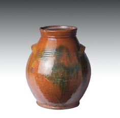 """BRISTOL COUNTY, MASSACHUSETTS GLAZED REDWARE STORAGE JAR, 1790-1830. """"  Sold: $ 1,121.00   """"Of ovoid form with molded neck and surrounded by three incised bands, applied lug handles, covered in pale orange glaze speckled in dark brown, and further embellished with green streaked patches. Height 11 inches.  Provenance: Ex-collection Al Benting, Barrington, New Hampshire."""""""
