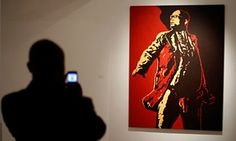 A visitor photographs a painting of South Africa's president Jacob Zuma