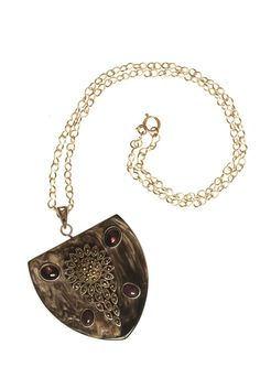 Penny Winter's large dark horn shield pendant with an antique silver charm flanked by three silver set African tourmalines with a silver chain