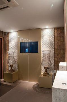 Volumes revestidos com chapas de alumínio (ACM) dourado exibem peças de design diferenciado e conferem o toque de requinte. Nas laterais, estão os painéis de madeira filetados, que se repetem no revestimento das paredes de toda a casa noturna.